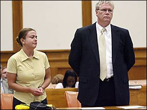 Nora Wallace, 33, of Toledo, and her attorney listen as Judge Denise Ann Dartt addresses her during her sentencing for embezzling more than $65,000 while she was employed at the Lucas County Jail from December through May. Wallace, who stole the money to pay bills and buy drugs, was given probation and was ordered to make restitution.