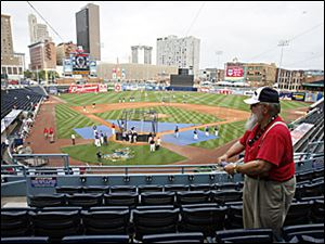 Ross Carr, 72, an usher at Fifth Third Field, cleans seats from yesterday's rain as the teams prepare for last night's Triple-A All-Star Game.