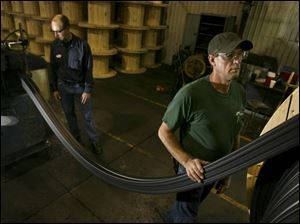 Larry Wilson, left, and Ray Clark, feed material from an extrusion line onto a large wooden spool.