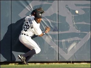 Tigers center fielder Curtis Granderson chases down a ball hit off the wall by Jermaine Dye of the White Sox.