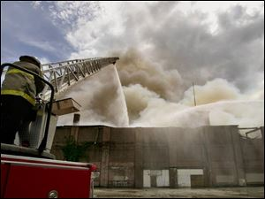 Firefighters pour water onto the three-story complex, which had been vacant for years. Firefighters did not enter the complex because it was considered too dangerous.