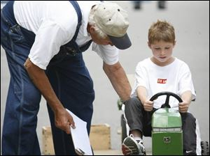 Garrison Moses, 7, prepares for a pedal-tractor pull with the guidance of Lou Mollett, a Williams County Fair board member.