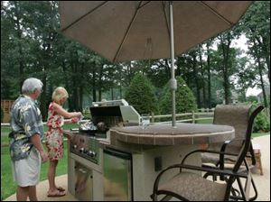 Rudy and Michellle Strom cook on the TEC grill on their patio.