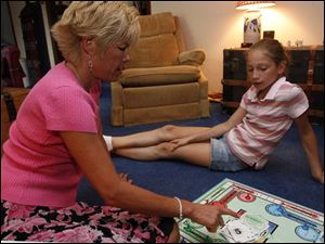 Cindy Hadsell plays a board game with her daughter, Lauren, 10, who will be starting fifth grade this fall.