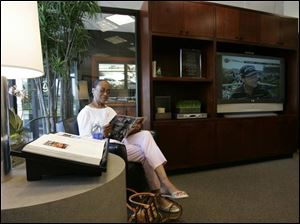 Vera Frazier reads in the lounge as she waits for her car to be serviced at the Sylvania Township Lexus dealership.