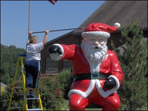 A worker freshens up the paint on the statue of Santa that stands outside Santa's Lodge hotel in Santa Claus, Ind.