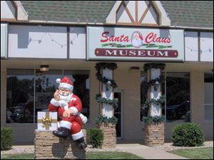 Santa welcomes visitors to the Santa Claus Museum, in Kringle Plaza in Santa Claus, Ind.