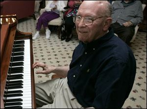 Olan Snavely, an Alzheimer's volunteer, tickles the keys at Sunset House before his appreciative listeners.