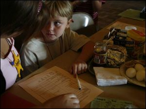 Alexis Bailey, 7, looks to Elizabeth Gilda for advice with her food list.