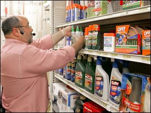Doug Janney restocks the shelves with anti-mosquito products at Janney's Ace hardware in West Toledo.