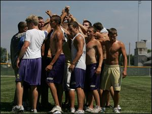 Maumee football players huddle up after a 30-minute workout. Strenuous activity, such as football conditioning drills, and summer heat can be a dangerous combination.