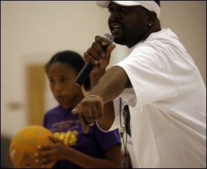 Coach Anthony Johnson calls a player out, above, during a kickball game at Bethlehem Baptist Church. The games are one way parents are making up for the cuts in funding to youth programs.