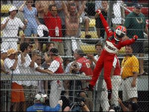 Helio Castroneves tacks on his signature victory celebration by climbing the fence at Michigan International Speedway after the Firestone 400.