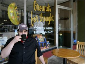 Mark Peterson of Bowling Green enjoys a cup of coffee outside Grounds for Thought on Main Street.