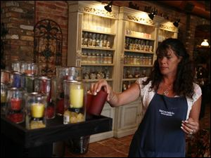 Beth Onofrey checks the stock in the Swan Creek Candle store in downtown's Warehouse District.