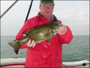 Toledo angler Dan Tucker hefts a 19-inch, 4 1/2-pound smallmouth bass taken in Lake Erie while fishing for yellow perch.