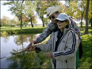 Dick Walle, one of the organizers of Reeling and Healing Inc., shows Sandra Geisert some of the finer points of fly-fishing for bass at Rockwell Springs Trout Club near Castalia while she is recovering from breast cancer.
