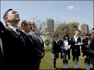 Jose Manuel Molina Garcia, the mayor of Toledo, Spain, at left, watches the flag-raising ceremony yesterday in International Park. Spanish offi cials began a five-day visit Saturday.