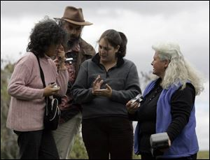 Lidia Senra of Spain, left, and Jean Cabaret of France listen as Lis Maguire of Food & Water Watch, a Washington-based activist group, interprets for Lynn Henning, a Michigan farmer.