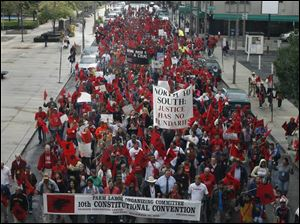 About 500 migrant workers who are delegates at the FLOC convention march from SeaGate Centre to the Lucas County Courthouse to rally for migrant and immigrant rights.