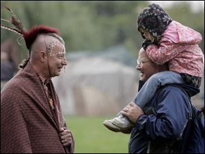 American Indian re-enactor Clarence Nieset talks with Eric Bell and his daughter, Carissa Bell, 4, at Buttonwood Park.