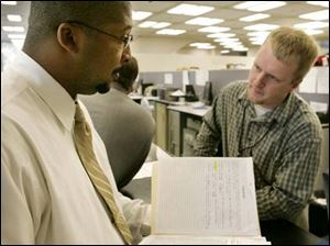 Agent Eric Hill, left, is aided by Deputy Clerk Lenny Tomanski at Toledo Municipal Court.