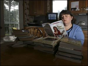 Dawn Trumbull of South Toledo looks through books she's swapping on the Internet.