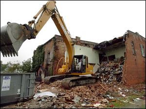Equipment operator Scott Apple demolishes a nuisance property on Sugar St. in Milton Center.