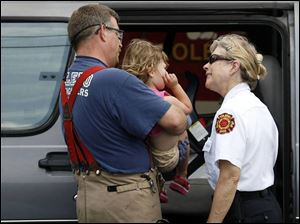Toledo firefighter Joe Clark and Battalion Chief Chris Davis comfort Karis Thomas, 2, who was a passenger in a van that was involved in a May 31 traffic accident in West Toledo.