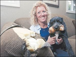 Kris Rockman and her dog, Cinder, with just one example of Cinder's handiwork, a torn sofa.