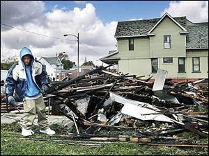 Tony Anderson removes some of the charred remains of a duplex on East Broadway.