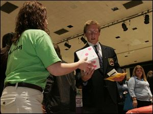 Priscilla Fleck, of the Fremont Federal Credit Union, hands Robby Yohe the die that yielded an $80 tire bill.