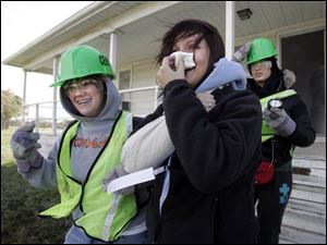 Tarah Couch, left, helps Becky Morris out of a smoke-filled house during the CERT drill at Owens Community College.