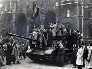 Hungarian revolutionaries wave their flag atop a captured Soviet tank during the brief moment of success before a massive USSR invasion on Nov. 4 crushed the rebellion.