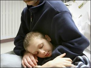 Trent Cousino hugs his son, Javan, 10, in a room at St. Vincent Mercy Medical Hospital as he talks about their tale of survival in Maumee Bay.