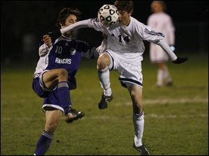St. John's Mark Witherell, left, and Lakewood's Veton Esati fight to gain control of the ball last night in a Division I regional soccer semifinal at Huron. St. John's won the game and will take a 12-6-3 record into Saturday's regional final against Strongsville, which defeated Perrysburg 3-0 last night at Medina.