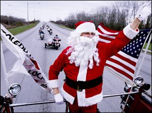 Larry Wulf, dressed as Santa, leads more than 800 motorcycles down Alexis Road on a mission to deliver toys to children.