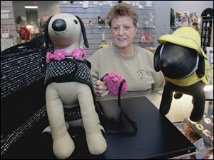 Nancy Poupard, at the Doggie Boutique in Perrysburg's Town Center at Levis Commons, shows off outerwear.