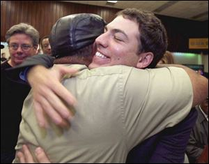 Ben Konop, right, is hugged by supporter Harold Stevens at the UAW Local 12 hall as the unof-