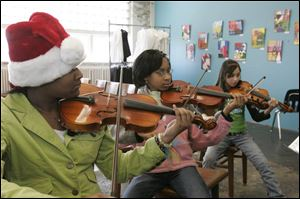 Practicing violin during an orchestra class at Toledo School for the Arts are, from left, Chafika Simmons, Richara Goss, and Taylor Ramos. The school is on 14th Street, near downtown.