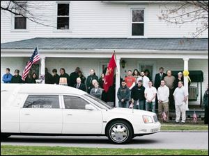 The hearse carrying his body passes his Green Springs home.