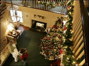Visitors to the Manor House at Wildwood Metropark take in the holiday decorations from the main staircase of the 68-year-old mansion. The former Stranahan home s annual Christmas display, in its 31st year, runs through Sunday.