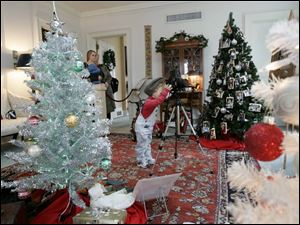 Kari Sweeney gets into the spirit of the  Snapshots of Christmas Past  display as her mother, Kathi Sweeney, left, watches.