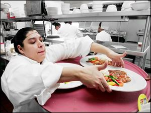 Jennifer Vasquez, who hopes to own a restaurant someday, loads a tray.