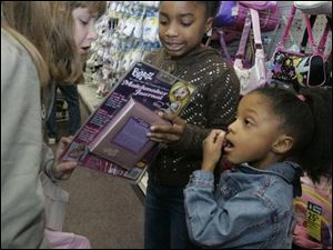 Out shopping, Laura Feltz, left, and Lindsay Haynes look over a journal that classmate Kaira Coburn found for her gift recipient as Kaira's sister, Kenya, watches.