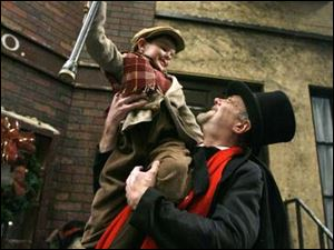 Paul Causman as Ebenezer Scrooge hoists Alexander Keck as Tiny Tim.