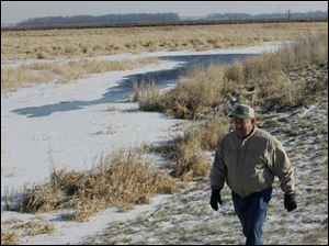 Fulton County farmer Colenzo Short surveys some of the 96 acres of wetland he preserved on his property near Fayette. He is being paid to capture greenhouse gases in the soil.