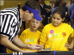 Referee Jeff Smith talks to Douglas Pienta, center, and Lydia Vergara about the score of their robot s performance. Douglas and Lydia are students at West Side Montessori Center.