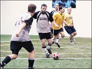 The Black Swamp soccer team, including Mark Hardy, second from left, takes on the Perrysburg Yellow Jackets at Gold Medal.