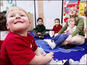 Jenny Smith of the Eastern YMCA plays a game with, from left, Antonio Cole, 4, Meraina Castillo, 4, and Alyssa Hudson, 3.